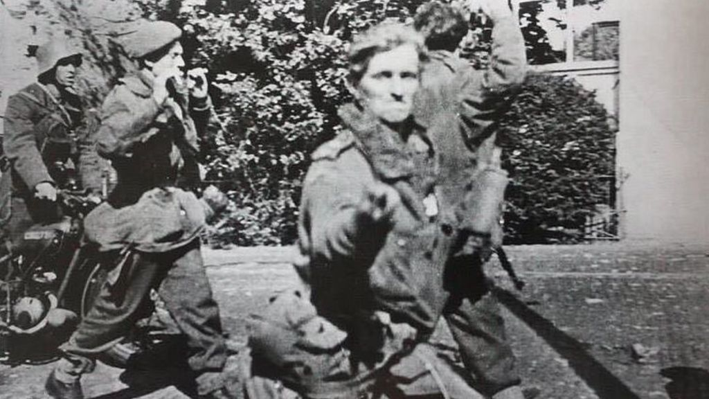 British soldier flicks V for Victory sign at German cameraman after capture.